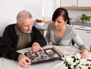 Eine junge Frau schaut mit Senioren ein Fotoalbum an